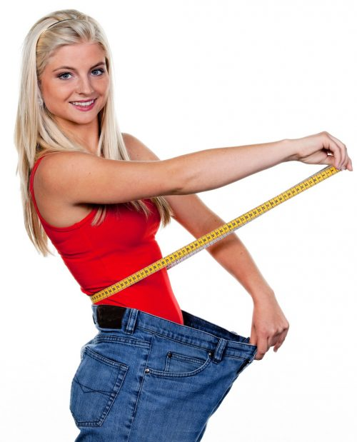 Woman in jeans too big for her holding measuring tape smiling into the camera