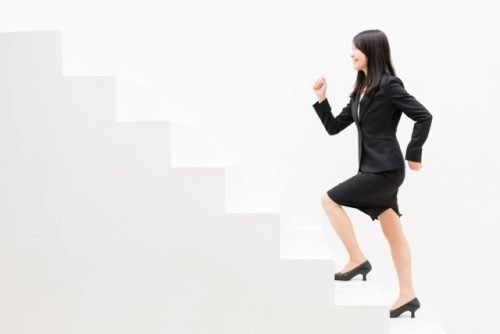 Smartly Dressed Happy Woman Marching Up White Stairs